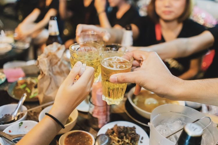 Cropped Friends Toasting Beer Glasses At Restaurant