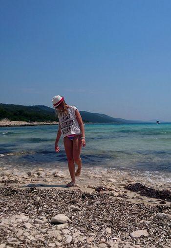 Full length of woman walking on beach against clear sky