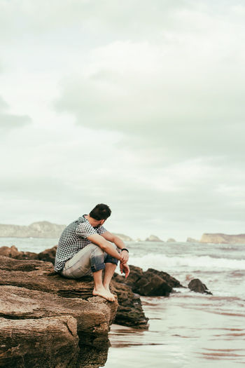 Side view of man sitting on rock against sea