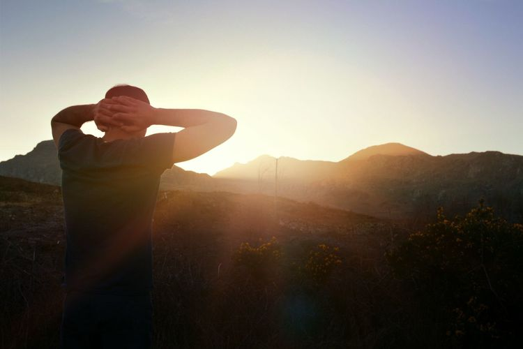 Rear View Of Man Standing With Hands Behind Head On Field Against Clear Sky During Sunset