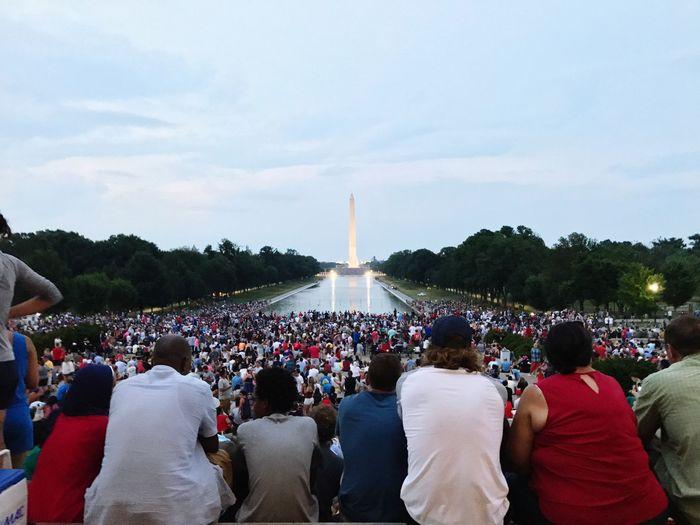 Crowd against illuminated washington monument at dusk
