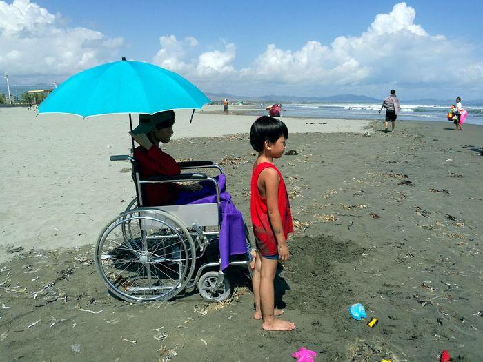 Boy sitting on beach against sky