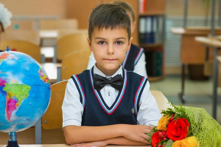Portrait of boy sitting at desk in office