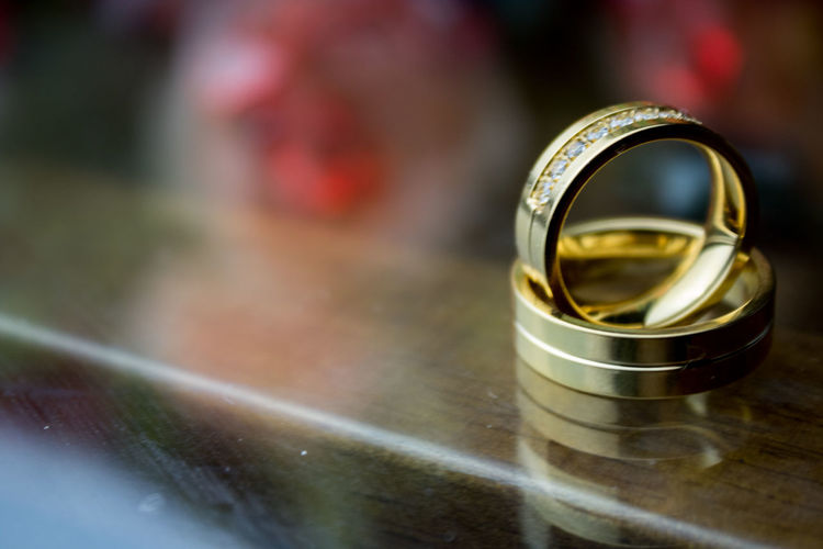 Close-Up Of Golden Wedding Rings On Table