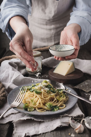 Midsection of woman preparing pasta with brussels sprout
