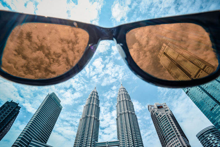Low angle view of sunglasses against modern buildings in city
