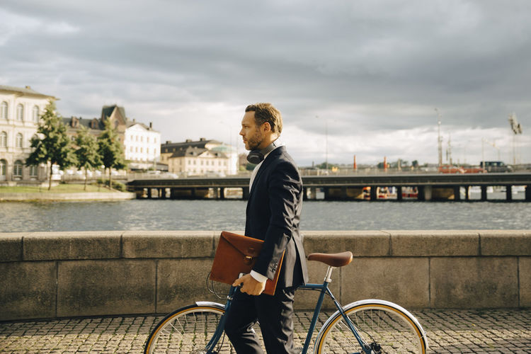 Man riding bicycle by river in city against sky