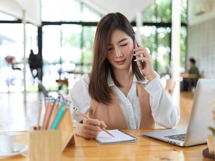 Smiling businesswoman talking on phone sitting at cafe