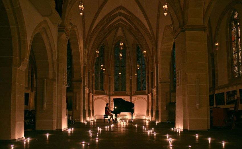 Woman Playing Piano In Illuminated Room