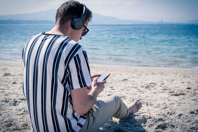 Relaxed man on the beach listening to music with his headphones