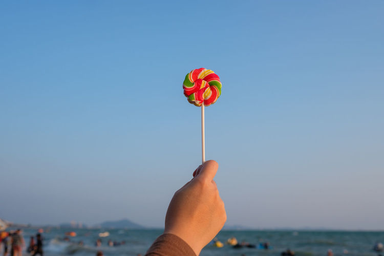 Cropped hand of woman holding lollipop at beach against clear sky