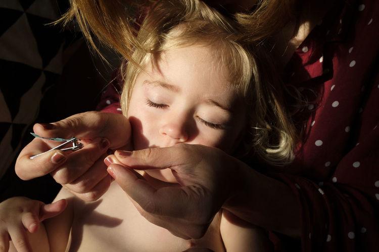 Close-up of woman cutting girl nail