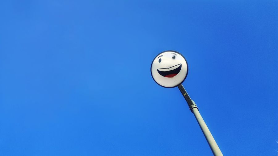 Low Angle View Of Anthropomorphic Smiley Face On Street Light Against Clear Blue Sky