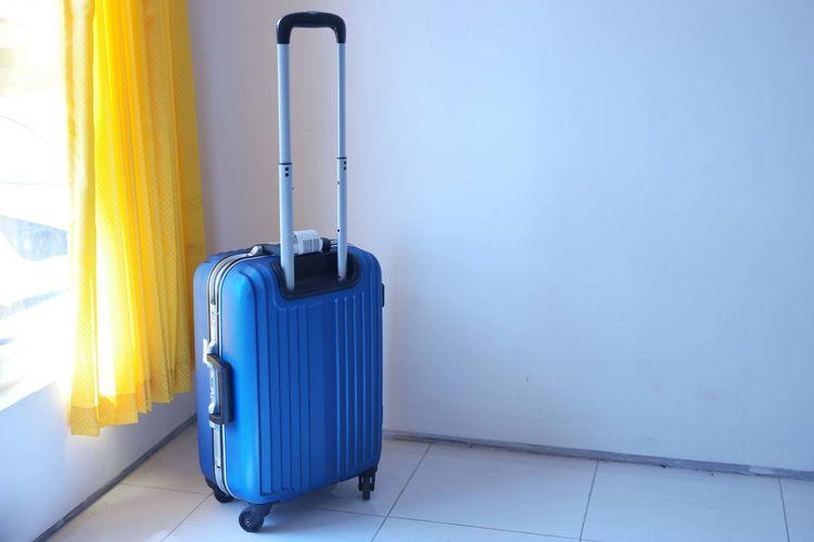 Blue metallic luggage in room