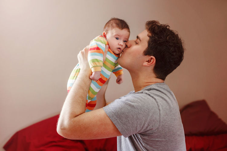 Side view of kissing baby boy at home