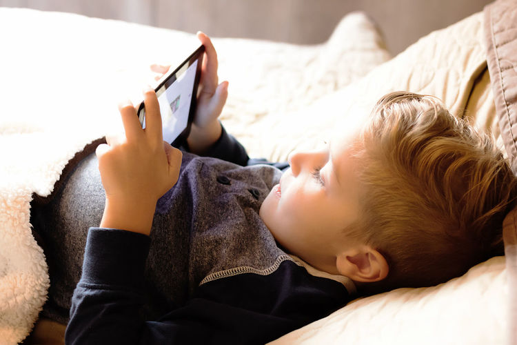 Midsection of boy using mobile phone while lying on bed