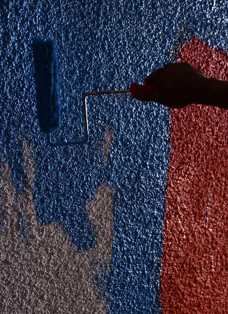 A painter's hand applies the next coat. Artist Blue Brush Hand Orange Painter Silhouette Textured  Wall