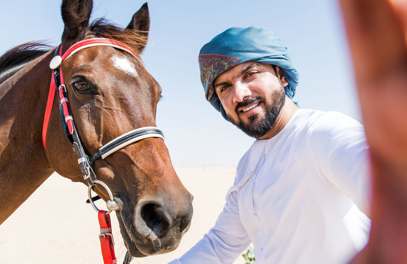 Portrait of smiling man with horse against clear sky