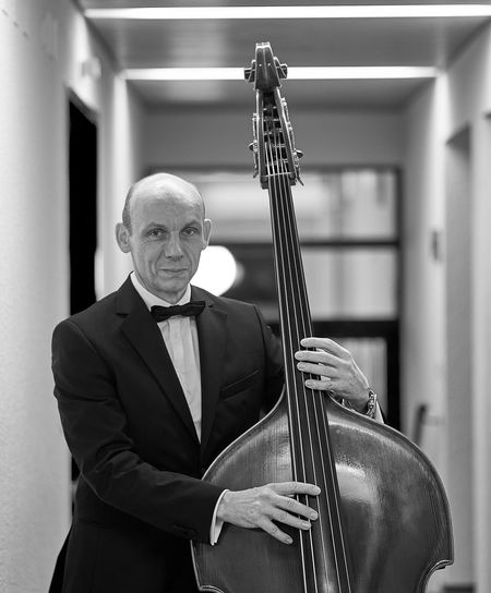 Portrait Of Smiling Mature Men Playing Double Bass At Hallway