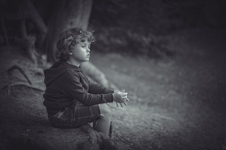 Side view of boy looking away while sitting on land
