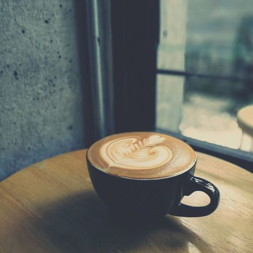 Close-Up Of Coffee Cup On Table By Window At Restaurant