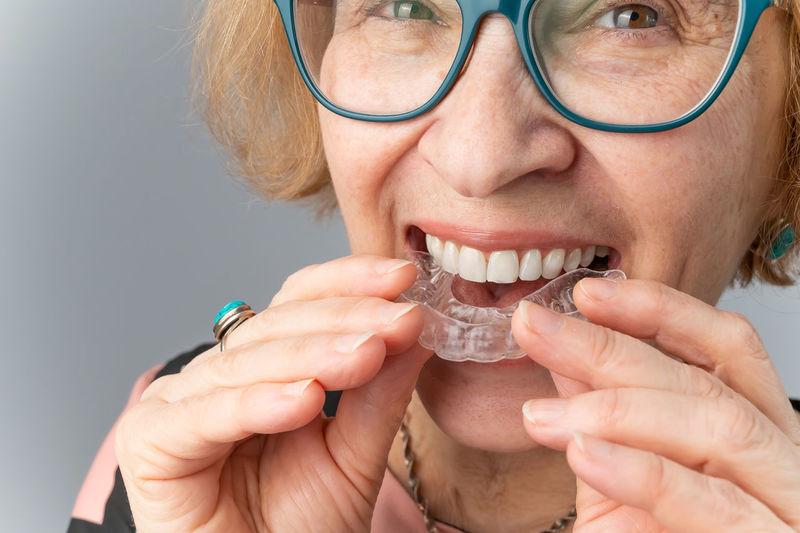Portrait of senior woman holding dental aligner