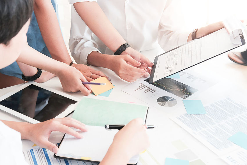 Business people Consulting and business planning. Adult Business Colleague Communication Connection Cooperation Coworker Group Of People Hand High Angle View Holding Human Hand Indoors  Men Midsection People Portable Information Device Real People Table Teamwork Technology Wireless Technology Women