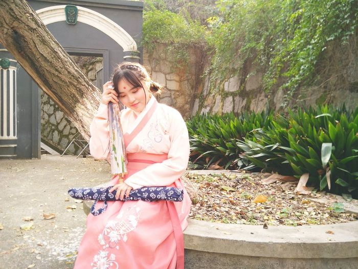 Young Woman In Kimono Sitting At Park