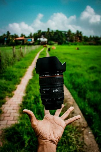 Cropped hand catching lens on grassy field