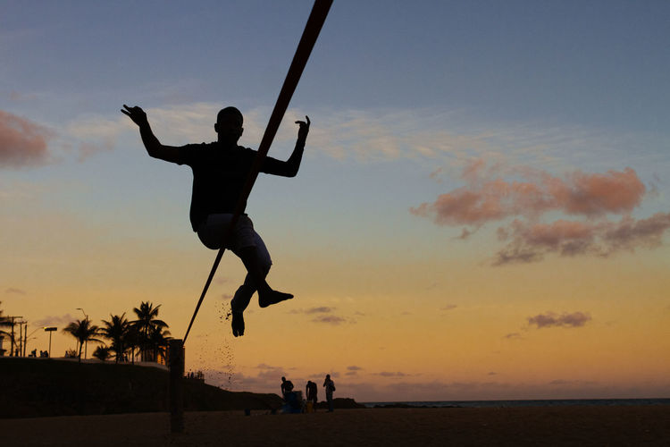 Full length of silhouette man jumping at beach against sky during sunset