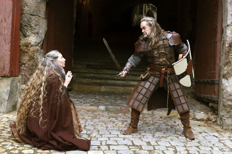 Man holding sword threatening woman outdoors