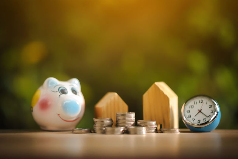 Stack Of Coins And Mode Houses By Piggy Bank On Table