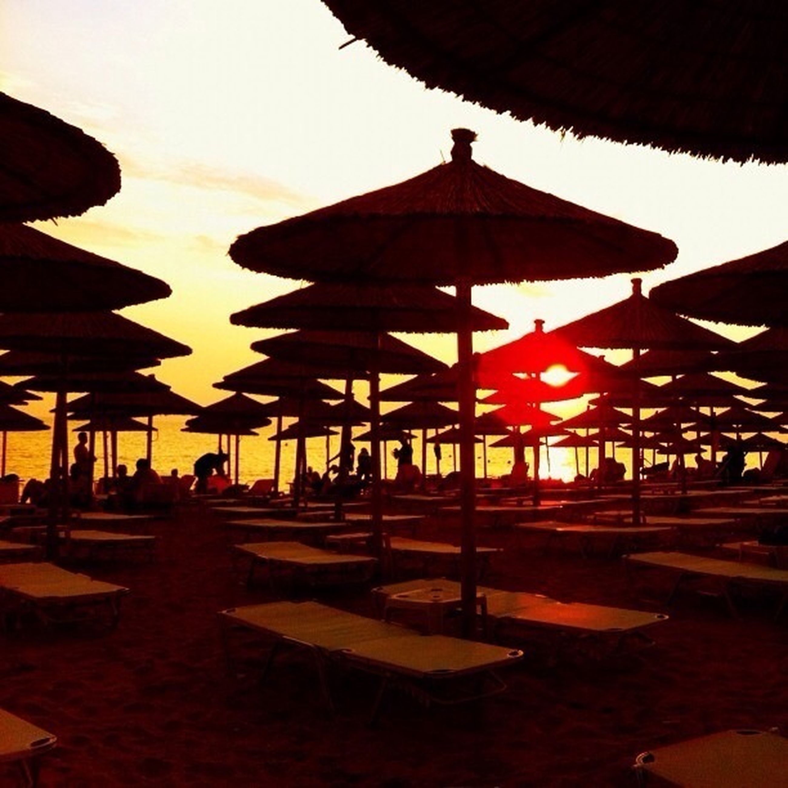 sunset, sea, beach, sky, built structure, incidental people, architecture, orange color, silhouette, sunlight, sand, illuminated, water, dusk, outdoors, shadow, travel destinations, in a row, horizon over water, travel