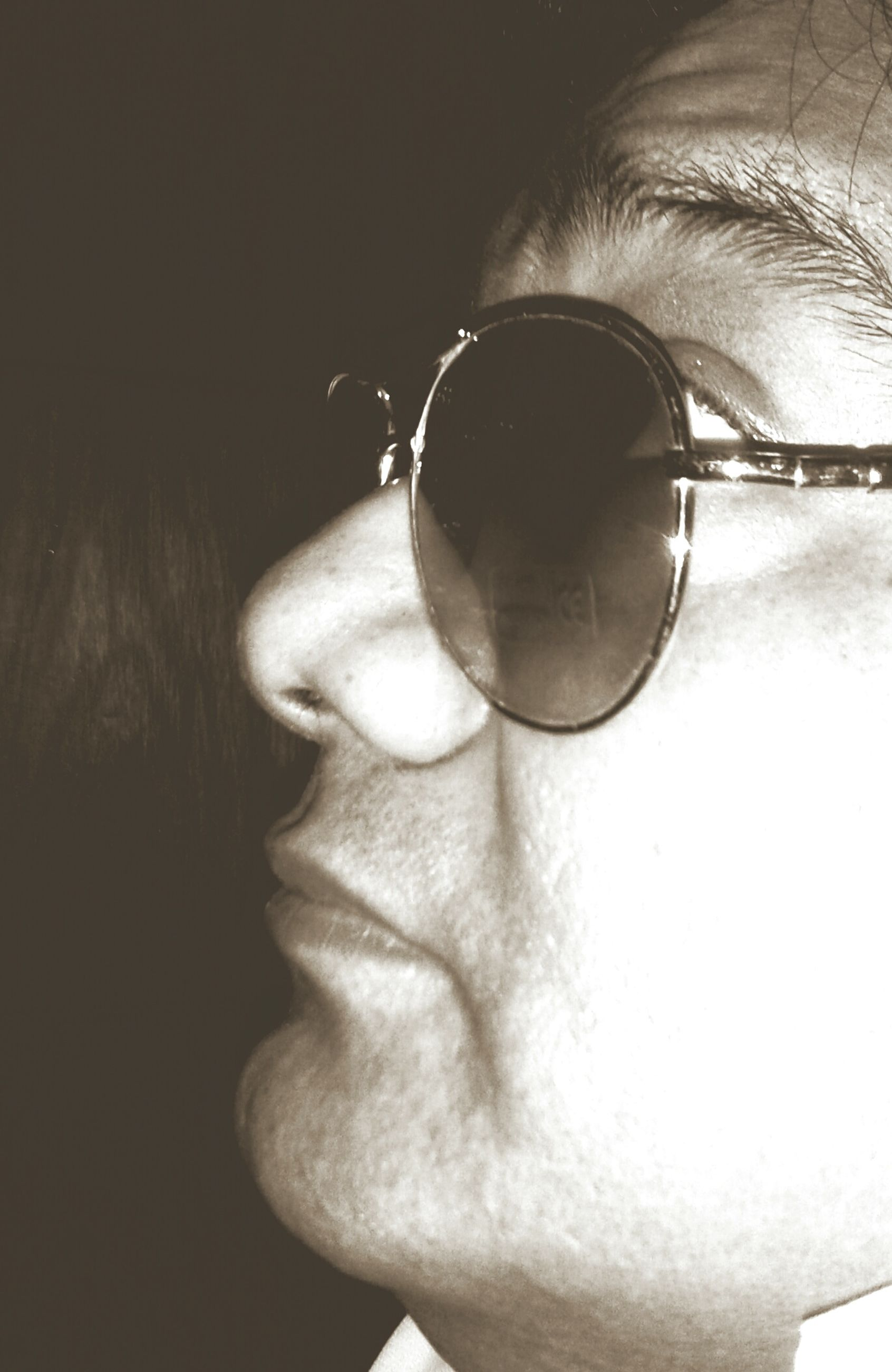 indoors, close-up, lifestyles, young adult, headshot, human face, sunglasses, person, leisure activity, front view, holding, eyeglasses, part of, looking at camera, reflection, portrait