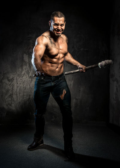 Full length of shirtless muscular man holding fire torch against wall