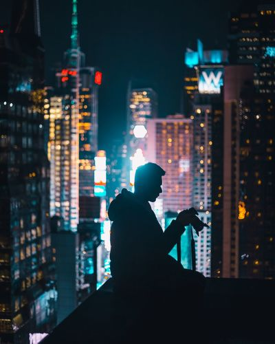 Silhouette of man in city at night