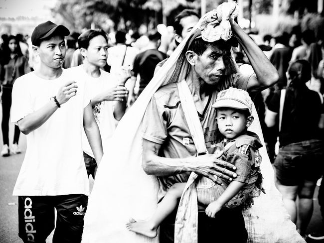 carrying baby while work Blackandwhite Photography Blackandwhite Streetphotography Street Photography Stretphotography Oldmanportrait Poor  Little Boy Kids The Street Photographer - 2018 EyeEm Awards Child Childhood Girls Arts Culture And Entertainment Crowd Togetherness Portrait Performance