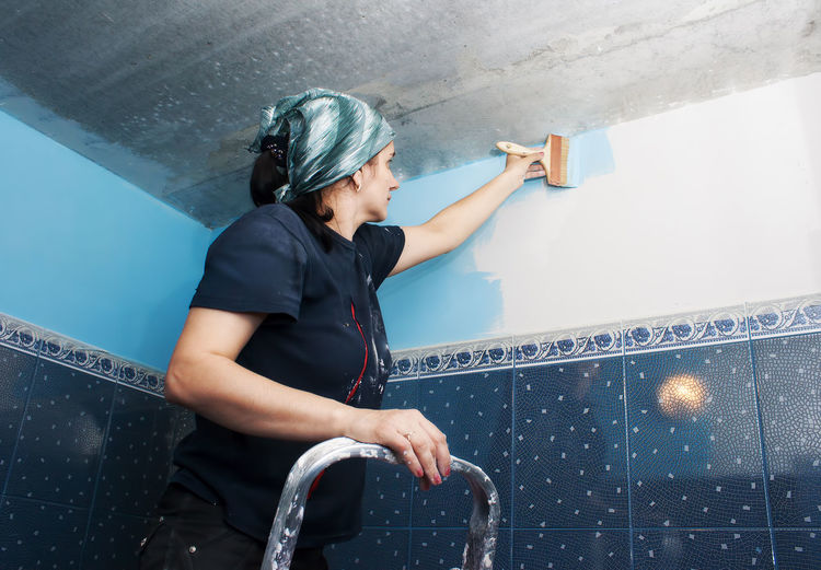 Woman painting wall at home