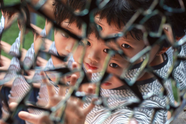 A boy looking in the pieces of broken mirror Care Fear Boy Boys Child Childhood Close-up Dangerous Day Headshot Indoors  Leisure Activity Lifestyles Pattern People Portrait Protection Real People Scared Selective Focus
