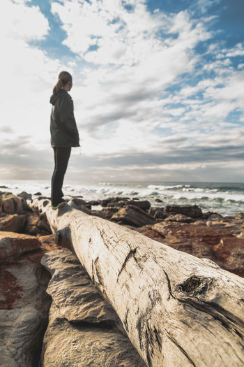 Side view of woman standing on log by sea against cloudy sky