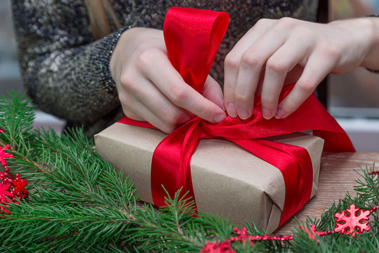 Christmas Gift Human Body Part Human Hand Christmas Present Ribbon - Sewing Item Wrapping Paper PresentHand Tied Bow Wrapped Celebration Giving Christmas Is Coming New Year Christmas Eve Red Ribbon Gift Box Christmas Preparation For Christmas Christmas Spirit Xmas Decorations Christmas Party Santa Christmas Decoration
