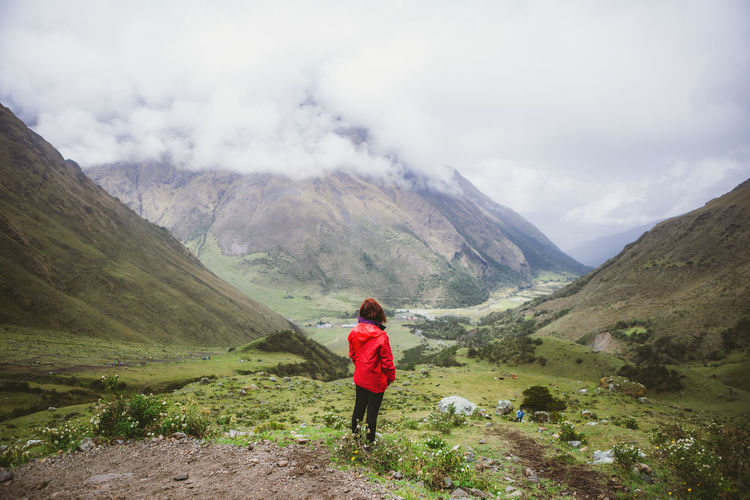 Rear view of woman on mountain against sky