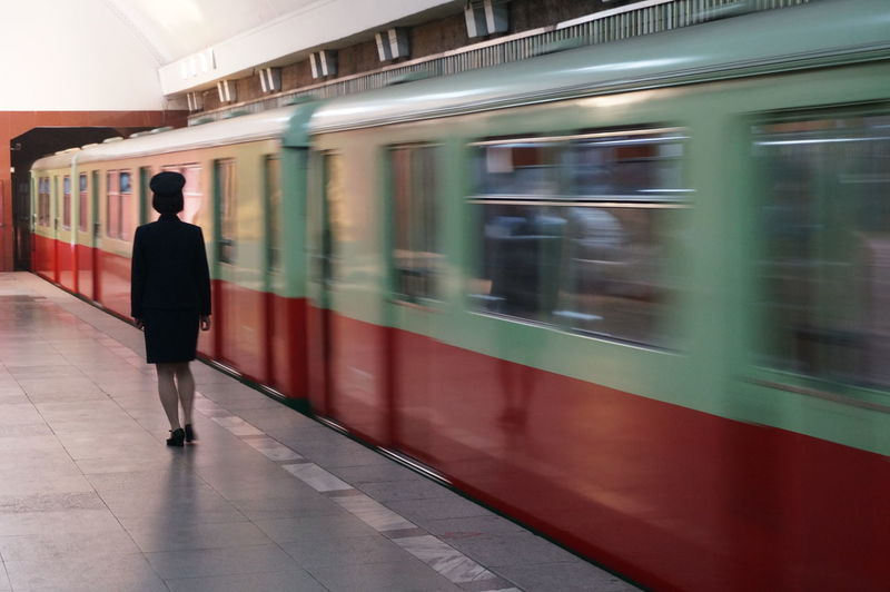 Blurred motion of train by woman standing at platform