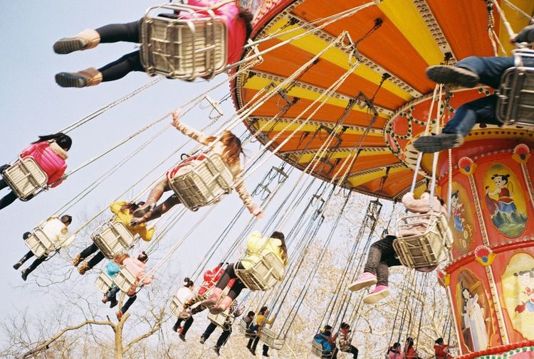 Low angle view of people enjoying on chain swing ride