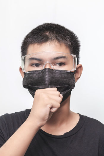 Portrait of teenage girl covering face against white background