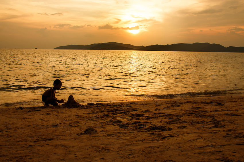 silhouette of people at the beach,The beauty of natural light at sunset. Beach Holiday Sunset Water Sky Sea Scenics - Nature Real People Beauty In Nature Lifestyles Outdoors Sunrise Orange Sky Love Children Family Happy Time Happiness People Sand Freinds Mountain Sea And Sky Silhouettes Women