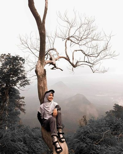 Man standing by bare tree on mountain against sky