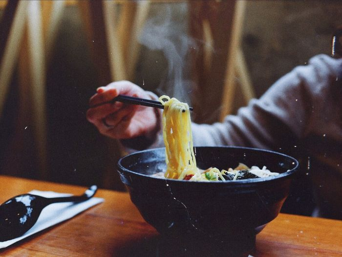 Cropped hand of person having noodles at home