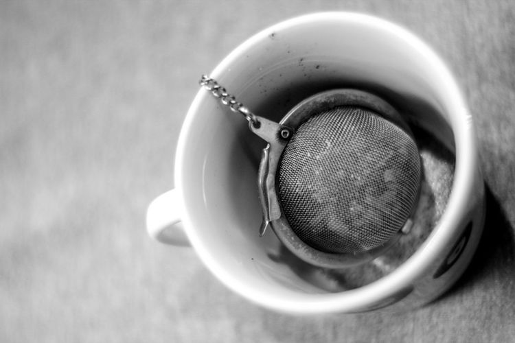 High angle view of tea strainer in cup on table