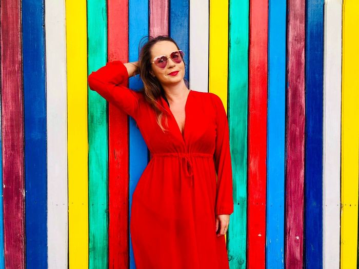 Portrait of woman in dress standing against multi colored wall